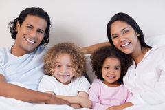 Smiling family sitting on the bed together Stock Photography