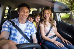 Smiling family sitting in the car. And driving Royalty Free Stock Photo