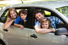 Smiling family sitting in a car. While looking outside Royalty Free Stock Photo