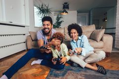 Family sitting on the couch together playing video games, selective focus royalty free stock image