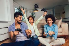 Family sitting on the couch together playing video games, selective focus royalty free stock images