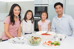 Smiling family sitting at dining table in kitchen. Portrait of a smiling family sitting at dining table in the kitchen at home stock photography