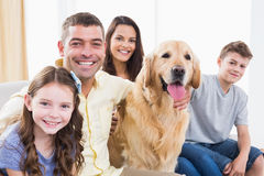 Smiling family sitting with Golden Retriever on sofa Stock Photo
