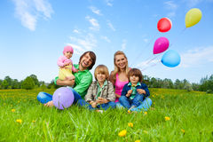 Smiling family sitting on grass with balloons Royalty Free Stock Photos