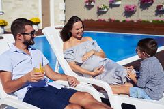 Smiling family sitting on lounge chairs in front of modern house stock image