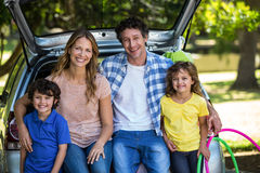 Smiling family sitting in the luggage space Royalty Free Stock Photo