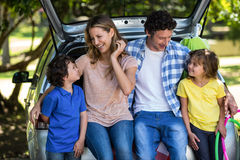 Smiling family sitting in the luggage space Stock Images