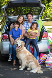 Smiling family sitting in the luggage space Stock Image