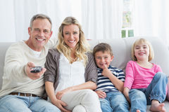 Smiling family sitting on sofa changing tv channel Royalty Free Stock Photography