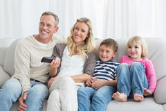 Smiling family sitting on sofa changing tv channel Stock Images