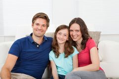 Smiling Family Sitting On Sofa Stock Photography