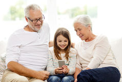 Smiling family with smartphone at home Royalty Free Stock Image