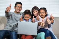 Smiling family on the sofa showing their thumbs up. Smiling family on the sofa with laptop showing their thumbs up Stock Photography