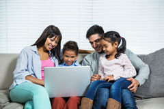 Smiling family on the sofa using laptop. In living room Stock Image