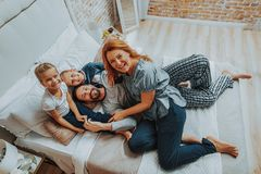 Smiling family spending time together in morning. Family relationship concept. Top view portrait of happy parents with their daughter and son laying on bed while stock images