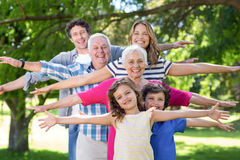Smiling family standing with arms stretched out Stock Images
