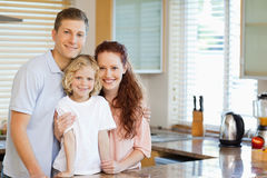 Smiling family standing behind the kitchen counter Royalty Free Stock Photography