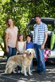 Smiling family standing in front of a car Royalty Free Stock Images