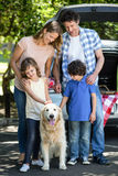 Smiling family standing in front of a car Royalty Free Stock Photos
