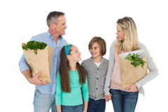 Smiling family standing holding bag of healthy groceries Stock Photo