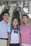 Smiling family standing next to the escalator near the subway station looking at camera, portrait royalty free stock images