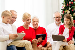 Smiling family with tablet pc computers at home. Family, holidays, christmas, technology and people concept - smiling family with tablet pc computers sitting on stock photo