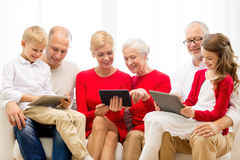 Smiling family with tablet pc computers at home. Family, holidays, christmas, technology and people concept - smiling family with tablet pc computers sitting on stock photos