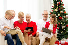 Smiling family with tablet pc computers at home. Family, holidays, christmas, technology and people concept - smiling family with tablet pc computers sitting on royalty free stock photos