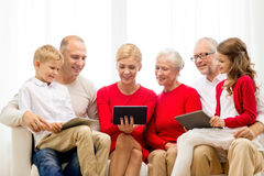 Smiling family with tablet pc computers at home. Family, holidays, christmas, technology and people concept - smiling family with tablet pc computers sitting on royalty free stock images