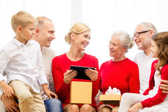 Smiling family with tablet pc and gift box at home Royalty Free Stock Images