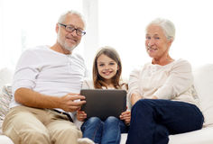 Smiling family with tablet pc at home Stock Photo