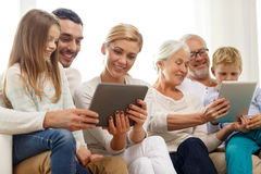 Smiling family with tablet pc at home Royalty Free Stock Images