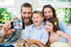 Smiling family taking selfie. In the living room Royalty Free Stock Photos