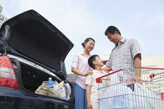 Smiling family talking and putting shopping bags into the car, outdoors Stock Photo