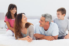 Smiling family talking together on bed Stock Images