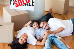 Smiling family in their new house lying on floor Stock Images