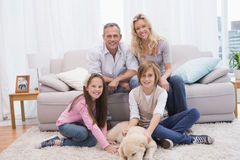 Smiling family with their pet yellow labrador on the rug. At home in the living room Royalty Free Stock Photo