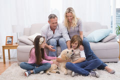Smiling family with their pet yellow labrador on the rug Royalty Free Stock Photos