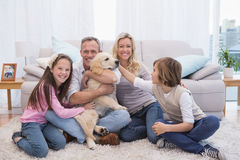 Smiling family with their pet yellow labrador on the rug. At home in the living room Stock Images