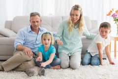 Smiling family with their rabbit on the rug Stock Photography