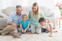 Smiling family with their rabbit on the rug Royalty Free Stock Photos