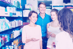 Smiling family of three consulting druggist. Smiling family of three persons consulting druggist in pharmacy. Focus on mature woman Royalty Free Stock Photo