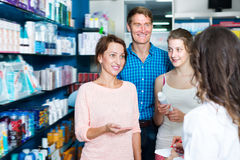 Smiling family of three consulting druggist. Smiling family of three persons consulting druggist in pharmacy. Focus on mature woman Stock Photo
