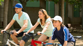 Smiling family of three cycling on city street Royalty Free Stock Photo
