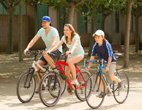 Smiling family of three cycling on street road Stock Images