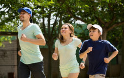 Smiling family of three running on sity street Royalty Free Stock Images