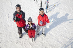 Smiling Family Throwing Snow Up in the Air in Ski Resort Royalty Free Stock Images