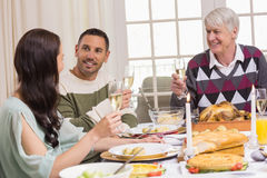 Smiling family toasting during christmas dinner Stock Image