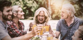 Smiling family toasting juice at table royalty free stock photos