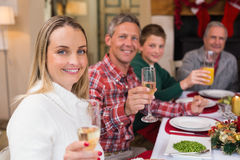 Smiling family toasting to camera during christmas dinner Royalty Free Stock Image